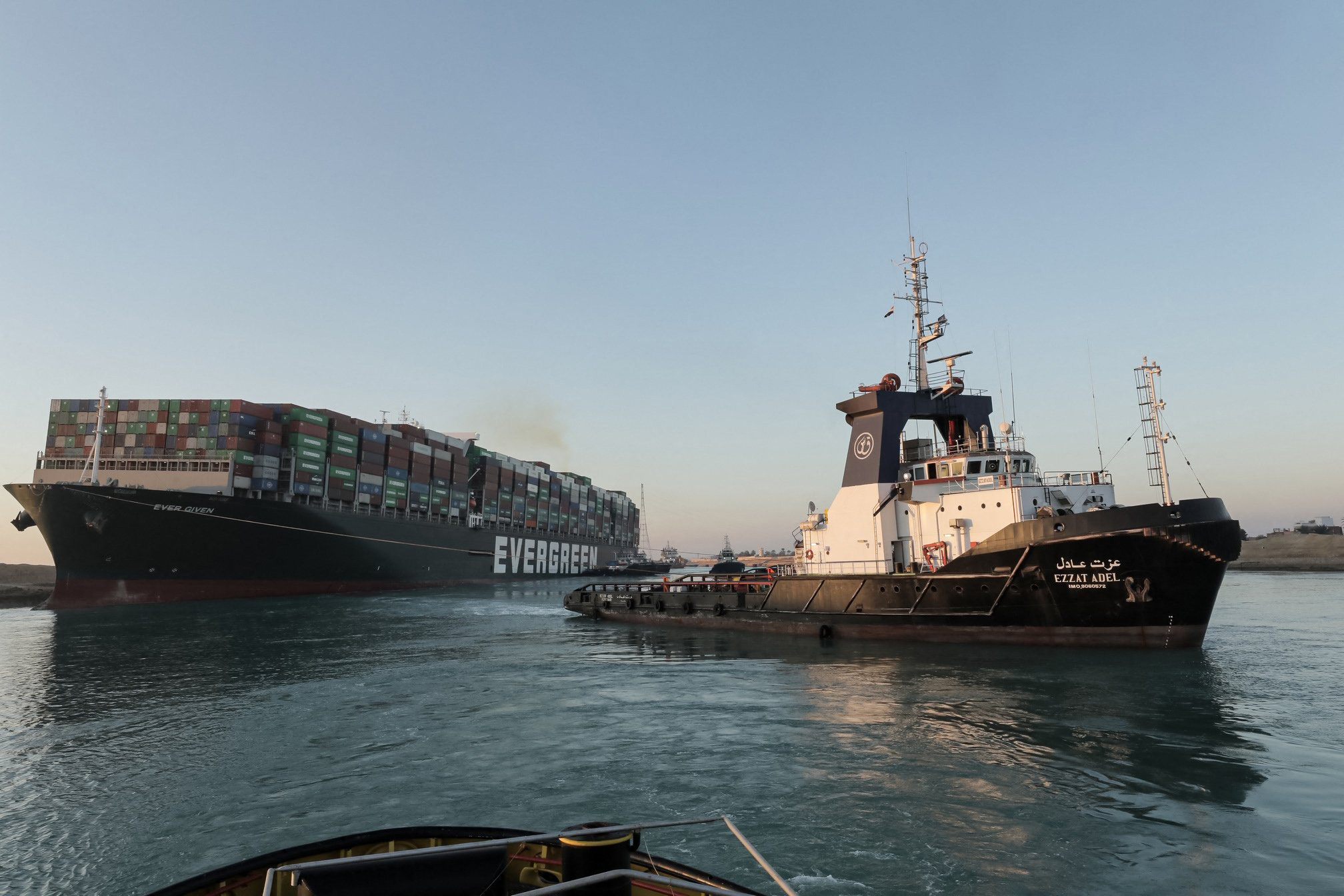 A handout picture released by the Suez Canal Authority on March 29, 2021, shows tugboats pulling the Panama-flagged MV 'Ever Given' container ship lodged sideways impeding traffic across Egypt's Suez Canal waterway.